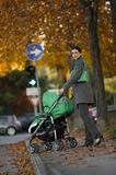 Young woman with baby carriage. Young woman walking her child through the city Royalty Free Stock Photo