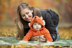 Young woman with baby dressed in fox costume Royalty Free Stock Images