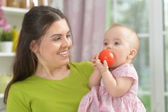 Young woman with  baby girl. Holding tomato Royalty Free Stock Image