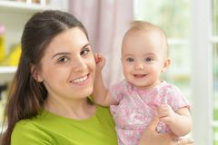 Young woman with  baby girl at home Stock Images