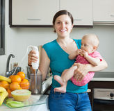Young woman with baby girl in kitchen Royalty Free Stock Photos