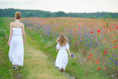 Young woman and baby girl in white dresses go on summer meadow i Stock Image