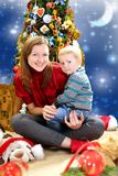 Young woman with a baby near Christmas tree. Stock Photography
