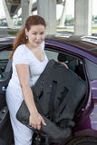 Young woman with baby safety seat placing in car. Young Caucasian woman with baby safety seat placing it in the car Royalty Free Stock Photo