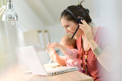 Young woman with baby working on laptop with headset Stock Photography