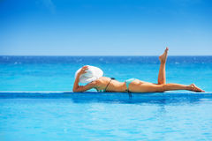 Young woman from back laying on board in ocean Royalty Free Stock Photography