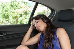 Young woman in back seat of car asleep with head against door Stock Image