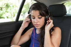 Young woman in back seat of car with black headphones Stock Photography
