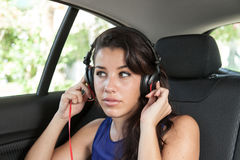 Young woman in back seat of car with black headphones Royalty Free Stock Images