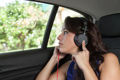 Young woman in back seat of car with black headphones Stock Images