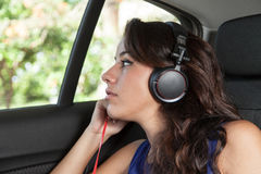 Young woman in back seat of car listening to music on black head Royalty Free Stock Photos
