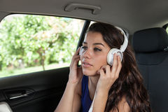 Young woman in back seat of car listening to music on white head Royalty Free Stock Photos