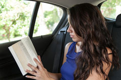 Young woman in back seat of car reading paperback Stock Photography