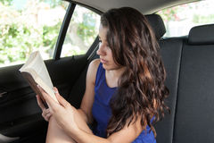 Young woman in back seat of car reading paperback Royalty Free Stock Image