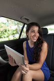 Young woman in back seat of car with tablet smiling at other pas Royalty Free Stock Photography