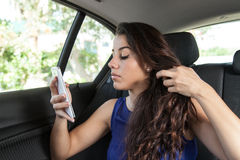 Young woman in back seat of car taking selfie Royalty Free Stock Photo