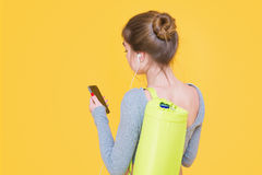 Young woman back view carrying yoga mat and listening to music Stock Photo