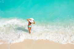 Young woman from back with white hat on the beach. Young woman from back with white hat in striped swimsuit standing in waves of ocean on the sand of beach Stock Photos