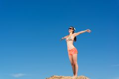 Young woman on a background of blue sky. Beautiful young woman standing on a background of blue sky with open arms Royalty Free Stock Photography