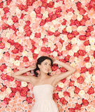 Young woman with background full of roses Royalty Free Stock Photos