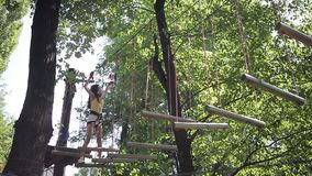 Girl on a rope climbing in park stock video footage