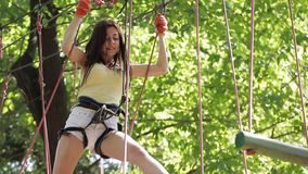Girl on a rope climbing in park stock footage
