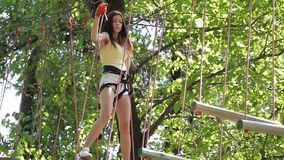 Girl on a rope climbing in park stock video