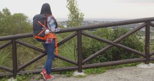 Young woman with a backpack admiring the scenery stock video footage