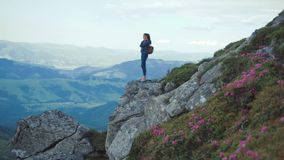Young woman with a backpack in casual wear stands on the edge of a mountain cliff high above, looks around thrilled stock video footage