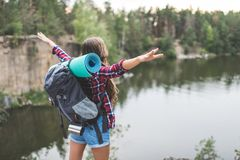 young woman with backpack celebrating freedom on nature while looking royalty free stock images