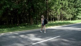 Young woman with backpack cross the road. Woman walking on the road. Young woman with backpack cross the road. Young woman traveler with backpack crossing the stock video footage