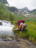 Young woman with backpack drinking from a stream Stock Photography