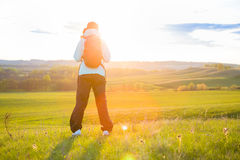 Young woman with backpack in a field. Stock Image