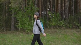 Young woman with a backpack in a hike is walking along a trail in the background of a forest.  stock footage