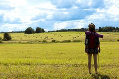 Young woman with backpack hiking in the countryside. Stress free travel concept. Beautiful lanscape Royalty Free Stock Photos