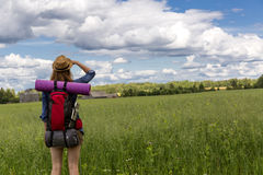 Young woman with backpack hiking in the countryside. Stress free travel concept. Stock Image