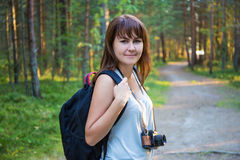 Young woman with backpack hiking in forest Stock Images