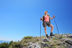 A young woman with backpack and hiking poles posing Stock Photos
