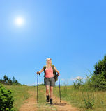 Young woman with backpack and hiking poles walking at sunny day Royalty Free Stock Photography