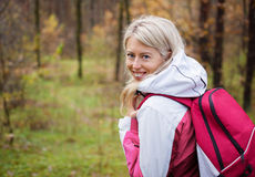 Young woman with backpack hiking in woods Royalty Free Stock Photography