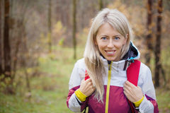 Young woman with backpack hiking in woods Royalty Free Stock Photos