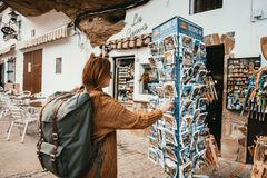 Young woman with backpack is looking at a postcard stand in a small spain village stock photo