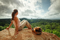 A young woman with a backpack is looking at the ruins of an anci Stock Images