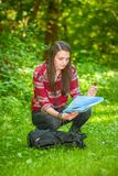 A young woman looks at a compass while hiking. A young woman with a backpack looks at a map and compass while hiking in the green forest Stock Images