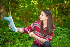 A young woman looks at a map while hiking. A young woman with a backpack looks at a map and compass while hiking in the green forest Royalty Free Stock Photography