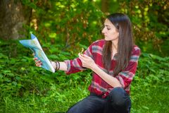A young woman looks at a map while hiking. A young woman with a backpack looks at a map and compass while hiking in the green forest Royalty Free Stock Image