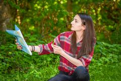 A young woman looks at a map while hiking. A young woman with a backpack looks at a map and compass while hiking in the green forest Stock Photos