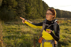 Young woman with backpack in a meadow showing way . Hiking at su Stock Photography