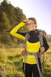 Young woman with backpack in a meadow watches way . Hiking at su Stock Photo