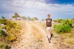 Young woman with backpack at mountain trail. Stock Images